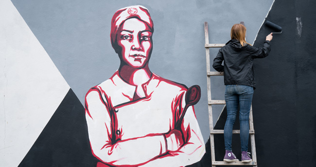 AMIGOS Gap student Audrey paints a mural as part of her internship.